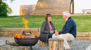 Two people sitting by a fire whilst glamping